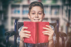 Portrait of disabled schoolboy holding book in library. At school Royalty Free Stock Image