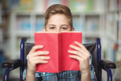 Portrait of disabled schoolboy holding book in library. At school Stock Photo