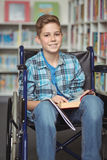 Portrait of disabled schoolboy holding book in library. At school Royalty Free Stock Images