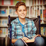 Portrait of disabled schoolboy holding book in library Royalty Free Stock Image