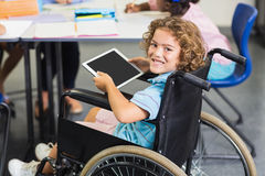 Portrait of disabled schoolboy using digital tablet. In classroom at school Royalty Free Stock Photography