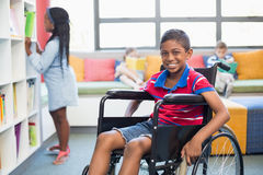 Portrait of disabled schoolboy on wheelchair in library. At school Stock Photo