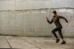 Portrait of disabled sportswoman with prosthetic leg in tracksuit, running outdoor along concrete wall. Portrait of disabled sportswoman with prosthetic leg in royalty free stock photo