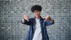 Portrait of disappointed girl showing thumbs-down on brick background. Portrait of disappointed girl with black curly hair and trendy glasses showing thumbs-down stock footage