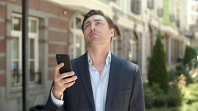 Portrait man using smartphone outdoor. Businessman typing on phone at street