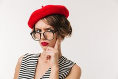 Portrait of a disappointed woman wearing red beret. And eyeglasses looking at camera isolated over white background Stock Photos