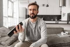 Portrait of a disappointed young man holding TV remote control Royalty Free Stock Image