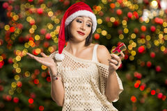 Portrait of disappointed young woman holding Christmas gift. Royalty Free Stock Image