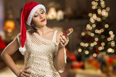 Portrait of disappointed young woman holding Christmas gift. Royalty Free Stock Photos