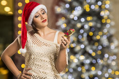 Portrait of disappointed young woman holding Christmas gift. Royalty Free Stock Photography