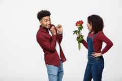 Portrait of a disappointed young woman holding red rose with while standing and angry on her boyfriend isolated over. Portrait of a disappointed young women Stock Photo