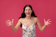 Portrait of a pretty young woman in a light dress standing on pink background in studio. People sincere emotions. Portrait of disappointed young woman in a stock photos