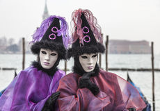 Portrait of a Disguised Couple. Venice, Italy- February 198th, 2012:Portrait of a couple disguised in Venetian costumes in front of gondolas dock during the Royalty Free Stock Image