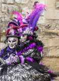 Portrait of a Disguised Couple. Annecy,France-March 15,2014:A couple disguised poses near a stones wall during the Annecy Venetian Carnival. Yearly in Annecy Royalty Free Stock Photos
