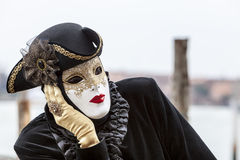 Portrait of a Disguised Person. Venice,Italy- March 2, 2014: Portrait od a disguised person with a white mask and black costume Royalty Free Stock Image