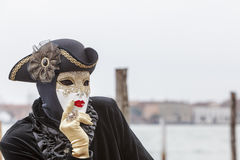 Portrait of a Disguised Person. Venice,Italy- March 2, 2014: Portrait of a disguised person with a white mask and black costume Stock Photos