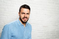 Facial Expressions Of Young Beard Man On Brick Wall. Portrait of disgusted man, hispanic guy showing disgust for bad smell or taste. Copy space stock photography