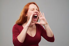 Portrait of disparate redhead woman loudly screaming. Close-up shot of disparate redhead woman loudly screaming or calling out someone. Holding two hands near Royalty Free Stock Photography