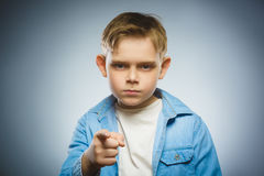 Portrait of displeased angry boy with threatens finger isolated on gray Stock Photography