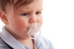 Portrait of displeased baby boy with pacifier Stock Photo