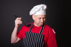 Portrait of the displeased cook with a ladle in his hand Royalty Free Stock Images