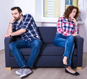Portrait of displeased couple sitting back to back in living roo Royalty Free Stock Images