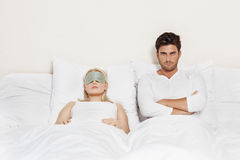 Portrait of displeased man with woman sleeping in bed Royalty Free Stock Image