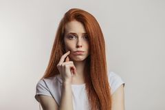 Portrait of displeased attractive redhaired woman isolated over white background. Portrait of displeased or offended attractive woman with perfect loose red hair royalty free stock image