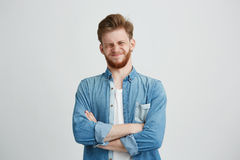 Portrait of displeased young handsome man in jean shirt with crossed arms over white background. Copy space Stock Images