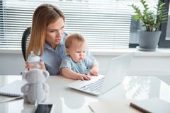 Discontented kid writing on keyboard near mother. Portrait of dissatisfied baby typing in laptop while sitting on arms of mom at desk. Woman looking at screen of royalty free stock photo