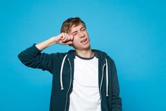 Portrait of dissatisfied disconcerted young man in casual clothes crying and wiping tears on blue wall royalty free stock photos