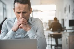 Unhappy worker watching at appliance. Portrait of dissatisfied male employer looking at gadget during job. Trouble at labor concept Royalty Free Stock Image