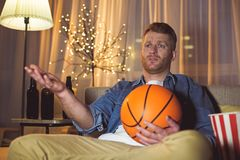 Discontented man watching television at home. Portrait of dissatisfied unshaven male looking basketball in digital device in apartment. Leisure concept royalty free stock image