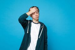 Portrait of dissatisfied young man in casual clothes putting hand on forehead, keeping eyes closed isolated on blue royalty free stock image
