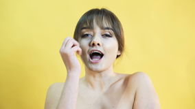 Portrait of the distorted girl with capricious emotion on yellow background 4K stock footage