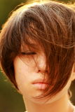 Portrait of a distressed korean, strands of hair cover face, eye. Close-up portrait of a sad, distressed beautiful brown, green tree background Royalty Free Stock Photography