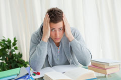 Portrait of a distressed student doing his homeworks. While holding his head Stock Photos