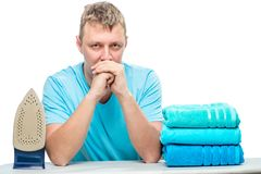 Portrait of a distressed tired man with a bunch of ironed towels royalty free stock photography