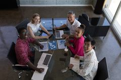 Business colleagues working together in office. Portrait of diverse business colleagues working together and looking over graphs in modern office royalty free stock image