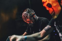 Portrait of Djs with skull masks playing mixing music at party festival. Fun, youth, entertainment and fest concept Stock Image