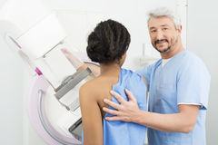 Portrait Of Doctor Assisting Patient Undergoing Mammogram Test Royalty Free Stock Images
