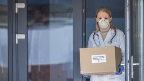 Portrait of a doctor with a box of protective medical masks.