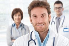 Portrait of doctor with colleagues behind. Portrait of happy male doctor with colleagues behind royalty free stock photos