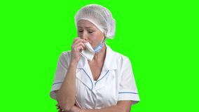 Portrait of doctor crying on green screen. Upset female doctor is crying on chroma key background. Human negative expressions stock footage
