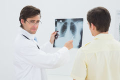 Portrait of a doctor explaining lungs xray to patient. Portrait of a male doctor explaining lungs xray to patient in the medical office stock photo