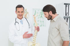Portrait of a doctor explaining the spine to a patient Royalty Free Stock Image