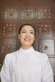 Portrait of Doctor In Front of Traditional Chinese Medicine Cabinet stock photo