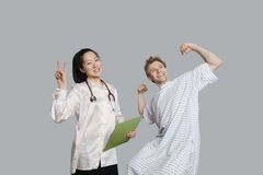 Portrait of doctor gesturing peace sign with patient cheering up Stock Photo