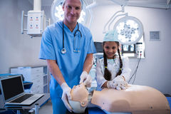 Portrait of doctor and girl examining a dummy Stock Image