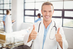 Portrait of doctor giving thumbs up and smiling Royalty Free Stock Images
